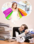 stock photo of sleeping bag  - Young secretary with a lot of folders sleeping and dreaming of shopping - JPG