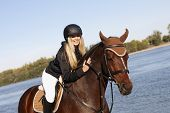 stock photo of fondling  - Happy female rider leaning over horse caressing back at riverside - JPG