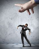 stock photo of male-domination  - Businessman marionette on ropes controlled by puppeteer - JPG
