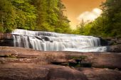 stock photo of backwoods  - Motion Blur Waterfalls Nature Landscape in Blue Ridge Mountains Sunset with green trees rusty natural orange rocks and flowing water - JPG