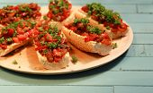 picture of antipasto  - Baguette with roasted vegetables hummus and parsley on wooden plate - JPG