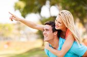 image of piggyback ride  - cheerful young couple piggyback and pointing outdoors - JPG