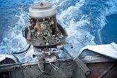 stock photo of outboard  - Old small boat outboard motor works without cover - JPG