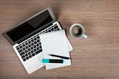 stock photo of pen  - Blank notepad over laptop and coffee cup on office wooden table - JPG