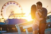 stock photo of romance  - romantic couple kissing at sunset in front of santa monica ferris wheel - JPG