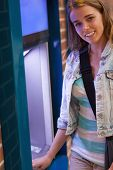 Pretty cheerful student withdrawing cash smiling at camera at an ATM