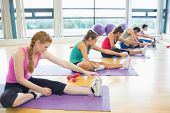 stock photo of slender legs  - Fitness class and instructor stretching legs in bright exercise room - JPG