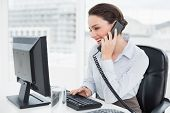 pic of tied hair  - Smiling elegant businesswoman using landline phone and computer in a bright office - JPG