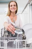 Lucky gorgeous model kneeling behind dish washer in bright kitchen