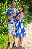 picture of amputee  - Happy attractive couple in love standing in a close embrace on a leafy green pathway with the man wearing a prosthetic leg following an amputation of his leg due to injury or disease - JPG