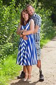 stock photo of amputee  - Joyful romantic young couple standing hugging each other on a rural path with a handsome disabled amputee with a prosthetic leg and a stylish young woman - JPG