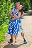 image of amputee  - Disabled man wearing a prosthetic leg and an attractive stylish young woman standing on a gravel path in loving hug looking at the camera with happy smiles - JPG
