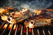 pic of ribs  - Rib steak on a hot grill BBQ with smoke and fire - JPG