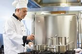 Focused head chef stirring in pot in professional kitchen