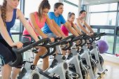 stock photo of exercise bike  - Determined five people working out at exercise bike class in gym - JPG