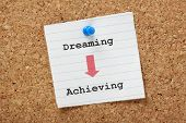 picture of transformation  - An arrow pointing the way from Dreaming to Achieving on a paper note pinned to a cork board - JPG