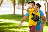 stock photo of role model  - Cute boy and his young father playing baseball outdoors at a park - JPG