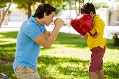 foto of boxing day  - Cute boy and his dad wearing boxing gloves and having fun outdoors - JPG