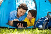 foto of role model  - Cute little boy and his dad using a tablet computer and relaxing on a tent on a camping trip - JPG