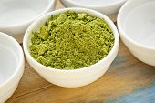image of moringa oleifera  - moringa leaf powder in a small bowl among empty white bowls - JPG