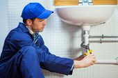 Attractive focused plumber repairing sink in public bathroom