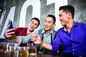 stock photo of club party  - Asian party people group of young friends taking pictures or selfies with their mobile or cell phone in fancy night club - JPG