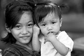 EL NIDO, PHILIPPINES, JANUARY 11 : Poor filipino little girl holding her younger sister, El Nido, Ph