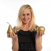 Attractive young blond woman with a warm friendly smile standing holding a golden pear and apple in