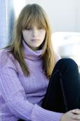 stock photo of teenage girl  - Young teenager girl sitting with her knee bent in sad depressed expression - JPG