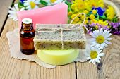 foto of tansy  - Oil in a bottle homemade soap on a piece of paper chamomile flowers tansy elecampane on the background of wooden boards - JPG