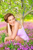 Cute happy girl sitting down beautiful fresh floral field in blooming garden, enjoying spring nature