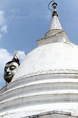 stock photo of vihara  - White dagoba and head of Buddha in Wewurukannala Vihara Sri Lanka - JPG