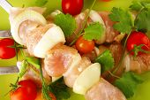 raw uncooked chicken shish kebabs with tomatoes on metal steel skewers on green plate isolated over