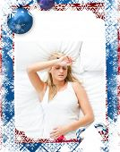 foto of sad christmas  - Upset woman having a migraine lying on a bed at home against christmas themed frame - JPG