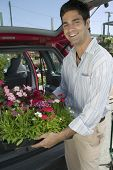 Man Loading Flowers into back of Van portrait