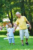 picture of grandfather  - happy grandfather and child have fun and play in park - JPG