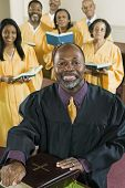 stock photo of minister  - Minister at altar with Bible gospel choir in background portrait - JPG
