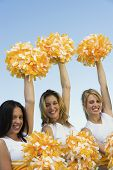 Three Cheerleaders rising pom-poms into the air (portrait)