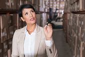stock photo of warehouse  - Warehouse manager checking her inventory in a large warehouse - JPG