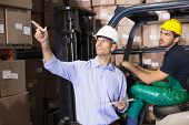 picture of forklift driver  - Warehouse manager talking with forklift driver in a large warehouse - JPG