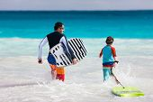 stock photo of boogie board  - Father and son running towards ocean with boogie boards having fun on beach vacation - JPG