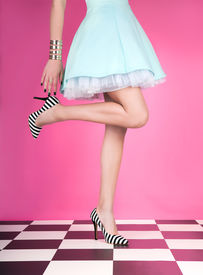 stock photo of up-skirt  - Young woman standing on one leg wearing high heels - JPG