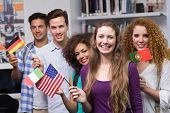 stock photo of waving  - Happy students waving international flags at the college - JPG