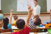 image of pupils  - Pupils raising hand during geography lesson in classroom at the elementary school - JPG