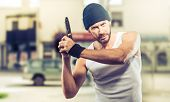 stock photo of cap gun  - Handsome aggressive criminal in the city street holding a gun - JPG