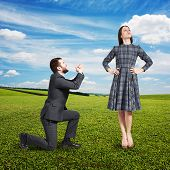 stock photo of forgiveness  - crying man looking at beautiful woman and asking for forgiveness - JPG