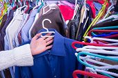 picture of stall  - Female hands choosing clothes on a market stall - JPG