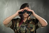 pic of camouflage  - Young woman wearing a camouflage uniform looking at the camera through binoculars - JPG