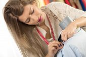 picture of tailoring  - Young beautiful woman with a sewing tape measure draped over the neck and straight pin in her mouth tailor clothes on a mannequin - JPG