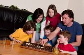stock photo of boardgame  - Big family is playing a boardgame in the livingroom - JPG